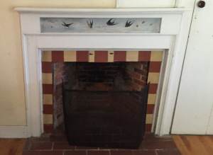 Tiled fireplace in Little Otie's room, with bird mural.